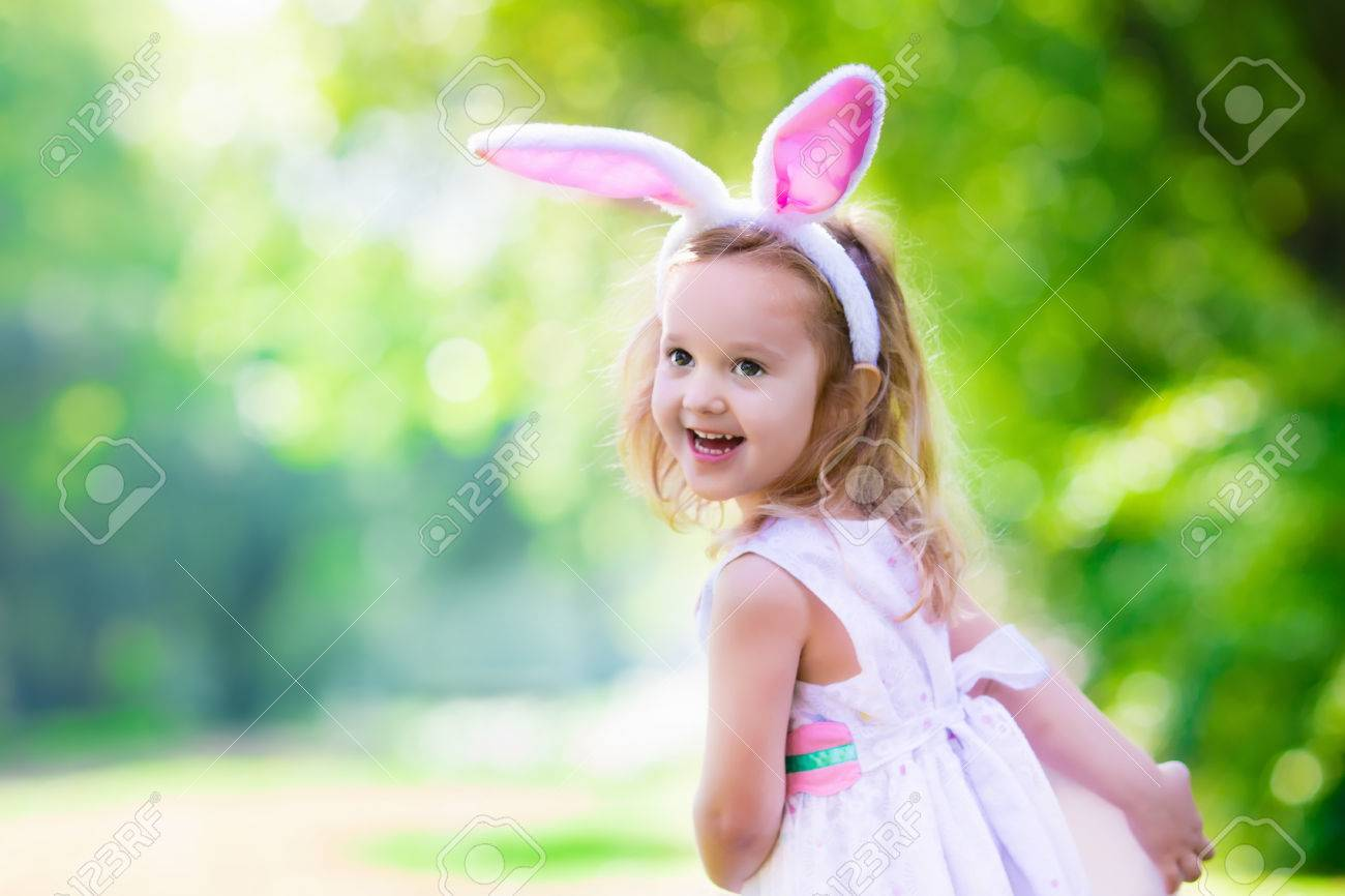 Little Girl Having Fun On Easter Egg Hunt Kids In Bunny Ears