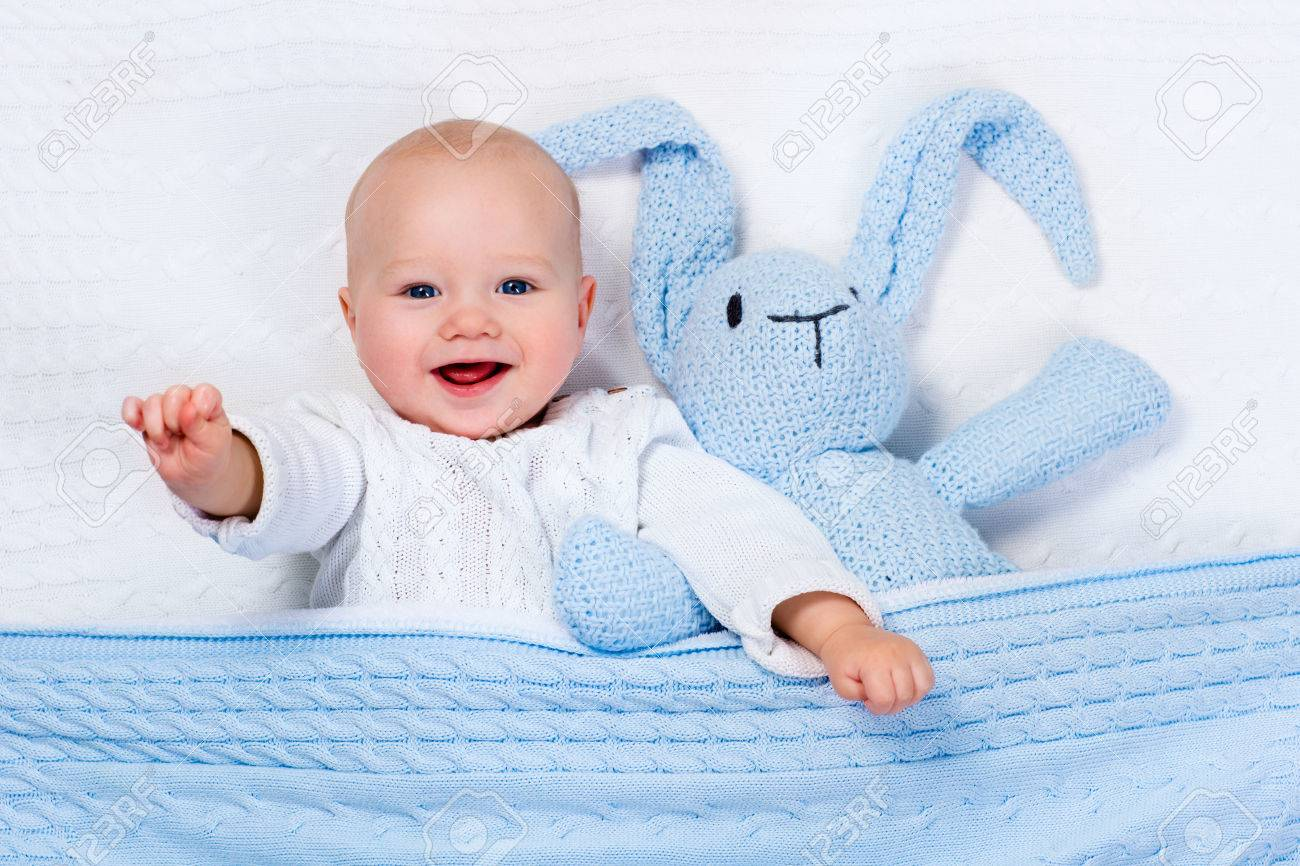 Funny little baby wearing a warm knitted jacket playing with toy bunny relaxing on white cable knit blanket in sunny nursery. Kids winter clothing and bedding. Hand made toys and textile for children. - 51358976