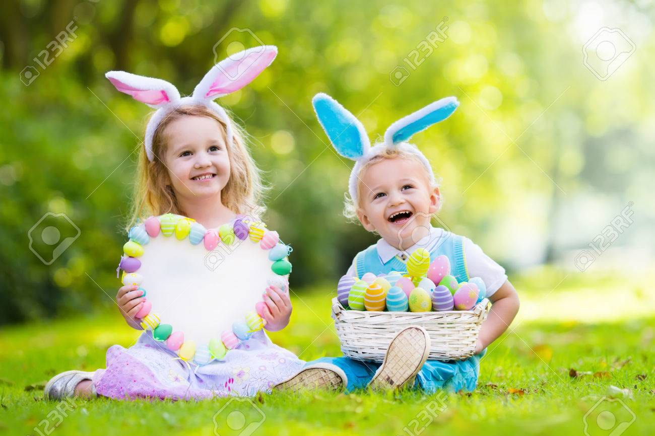 Little Boy And Girl Having Fun On Easter Egg Hunt Kids In Bunny