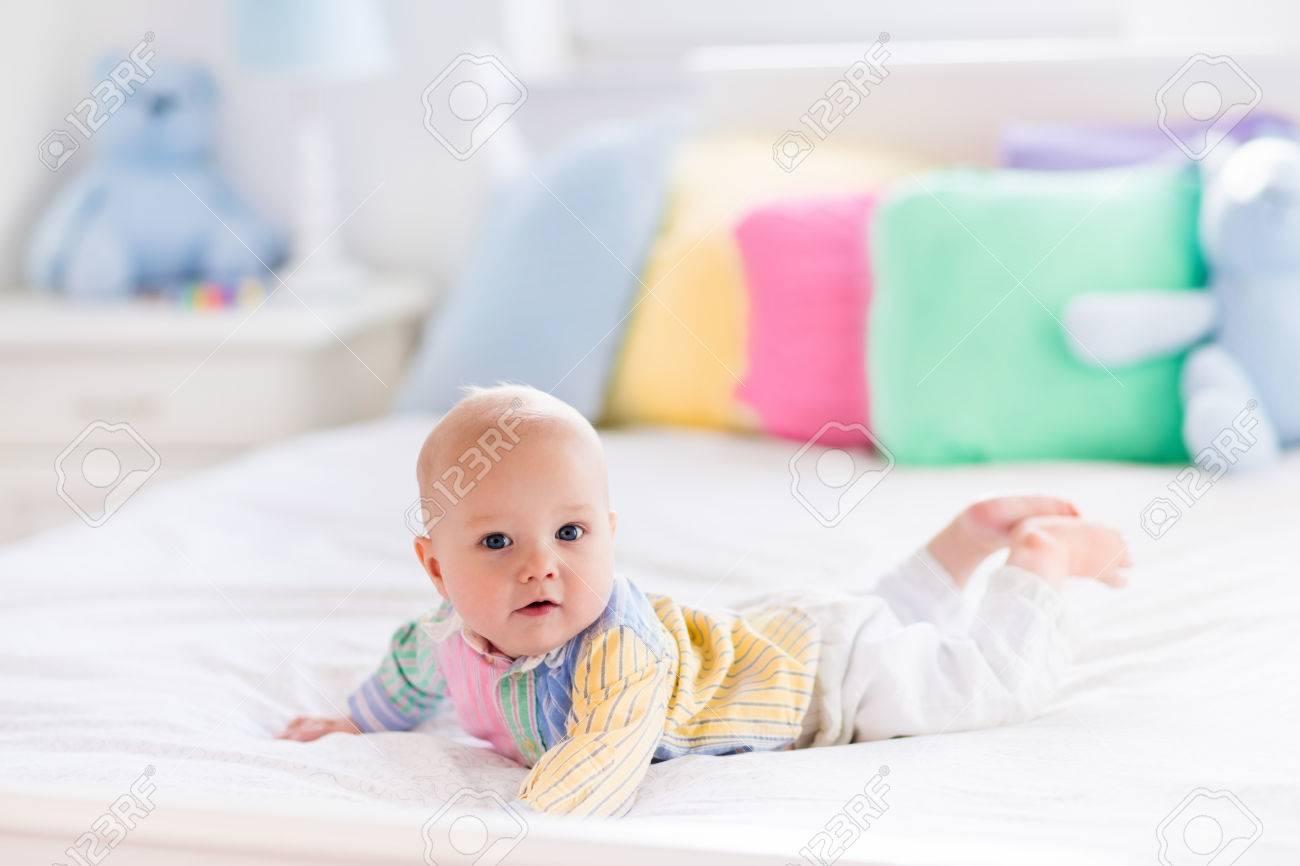 Baby Im Weißen Schlafzimmer. Neugeborenes Kind Im Bett Mit Pastellfarbenen  Kissen. Kindergarten Für Kinder