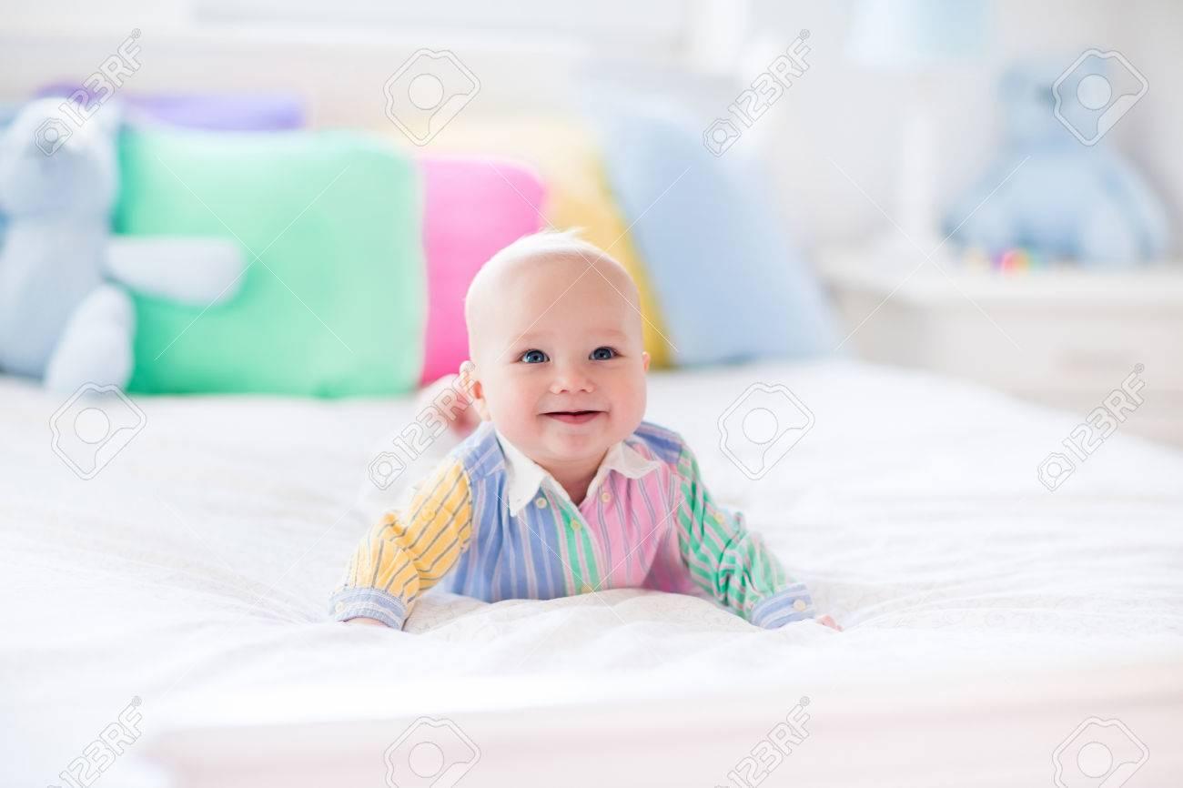 Baby jongen in het wit slaapkamer. pasgeboren kind in bed met pastel