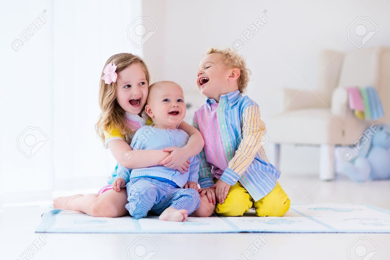 Group of three kids playing in a white bedroom. Children play at home. Preschooler girl, toddler boy and baby in nursery. Happy little brothers and sister bonding having fun together. Siblings love. - 52849309