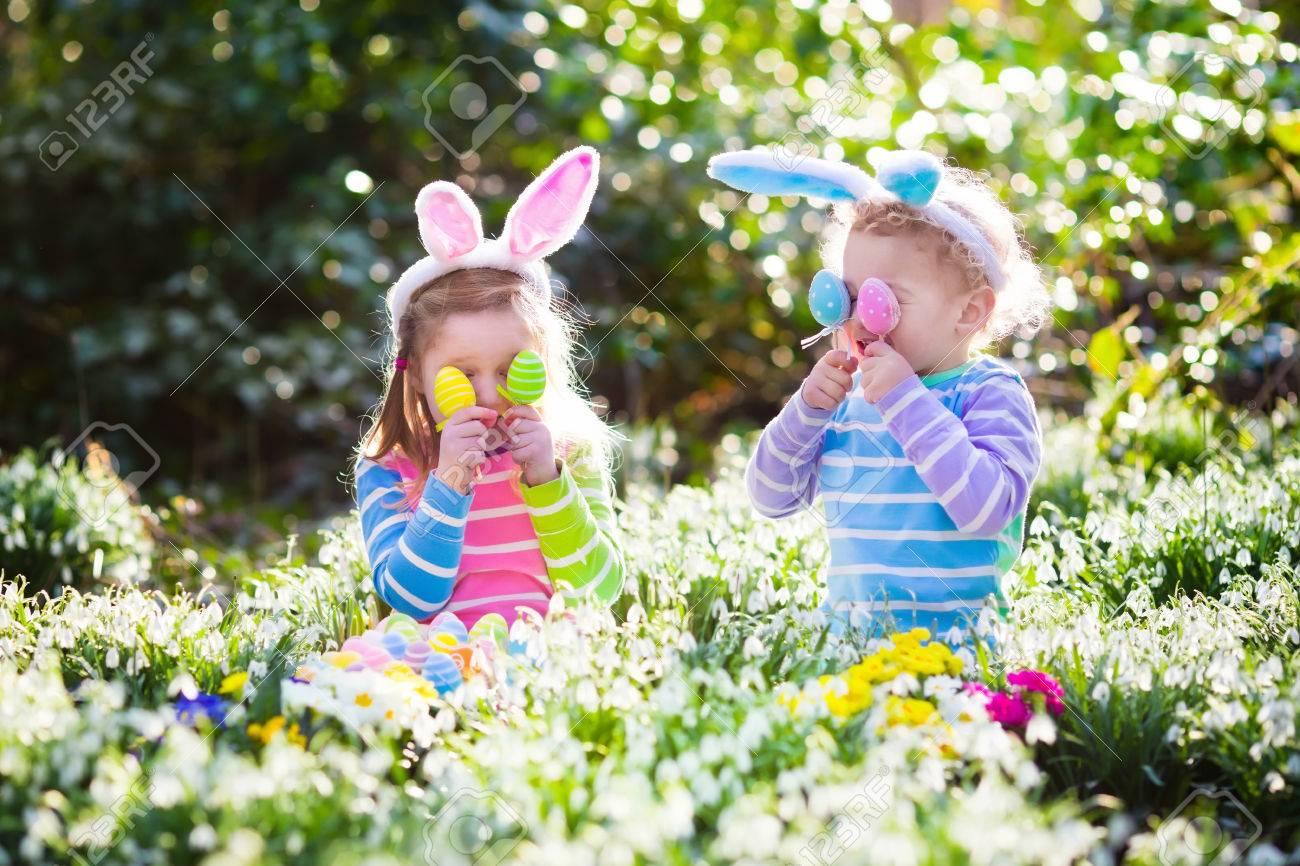 kids on easter egg hunt in blooming spring garden children with