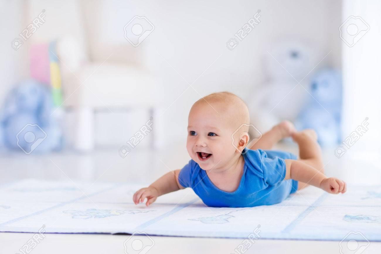 Schattige baby jongen in het wit zonnige slaapkamer pasgeboren