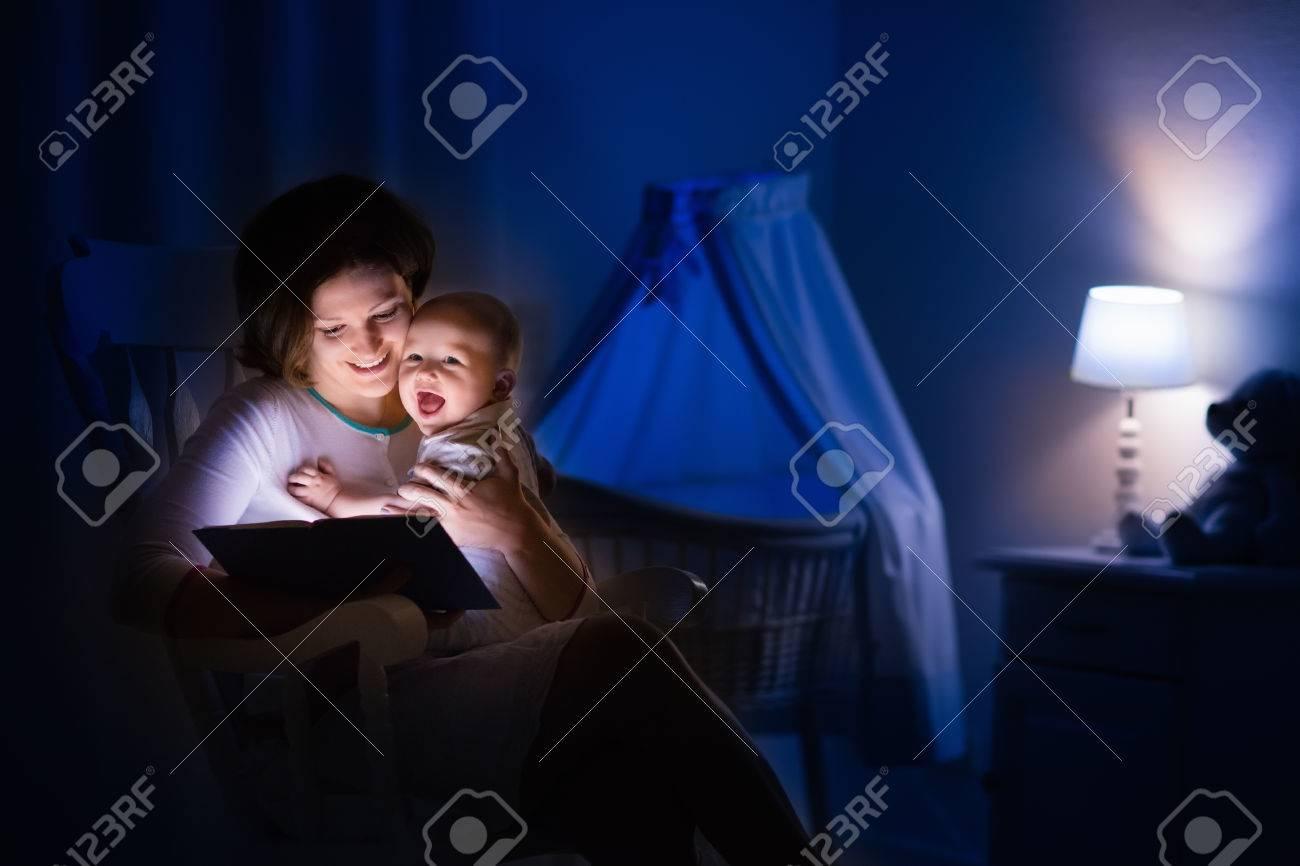 mère et bébé lisant un livre dans la chambre sombre. maman et enfant
