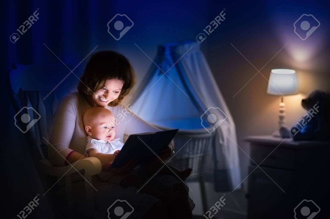 Reading lamp stock photos royalty free reading lamp images mother and baby reading a book in dark bedroom mom and child read books before sciox Gallery
