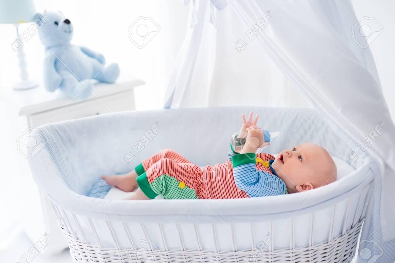 Lustige Baby In Bunten Pyjama Mit Flasche Trinkwasser Oder Milch In Weißen  Krippe Mit Baldachin.