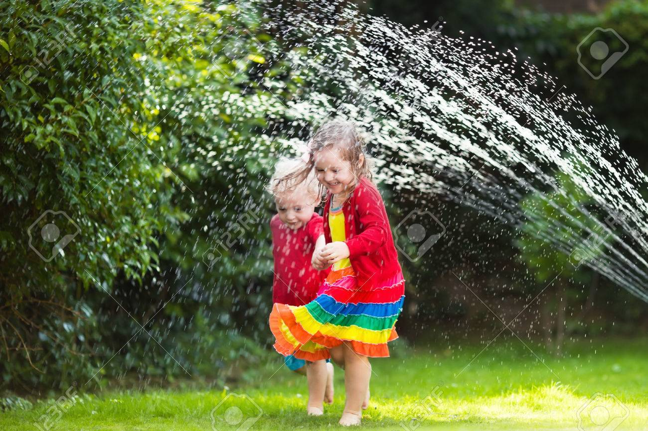 child playing with garden sprinkler preschooler kid running