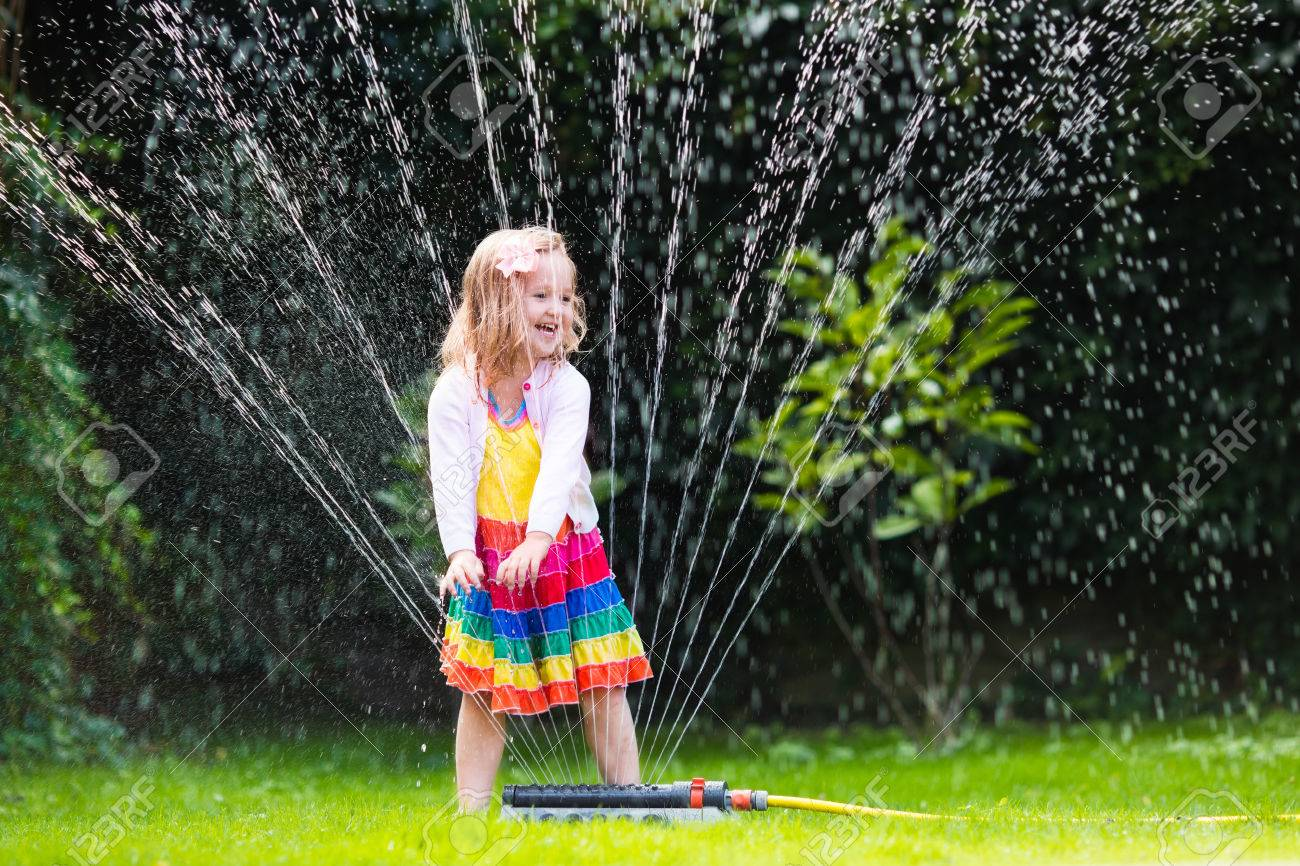 kids play water Child playing with garden sprinkler. Preschooler kid running and jumping.  Summer outdoor water fun