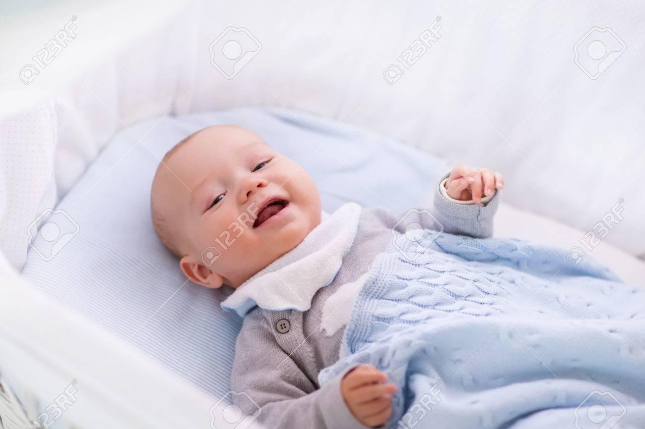 594b972fb Bebé Recién Nacido En La Cama. Niño Recién Nacido Durmiendo Bajo Una Manta  De Punto Blanco. Duermen Los Niños. Ropa De Cama Para Los Niños.