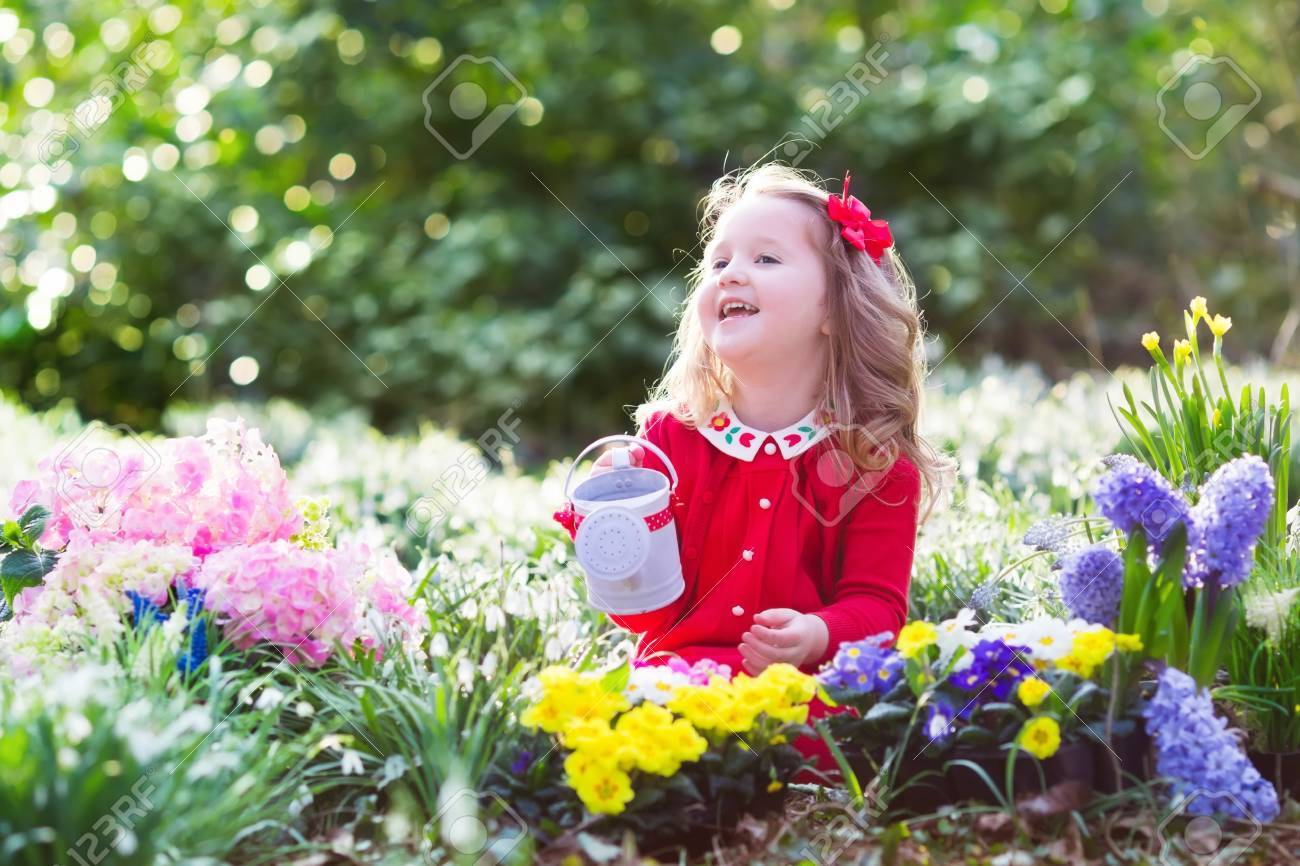 Child planting spring flowers in sunny garden little girl gardener child planting spring flowers in sunny garden little girl gardener plants hyacinth daffodil mightylinksfo Image collections