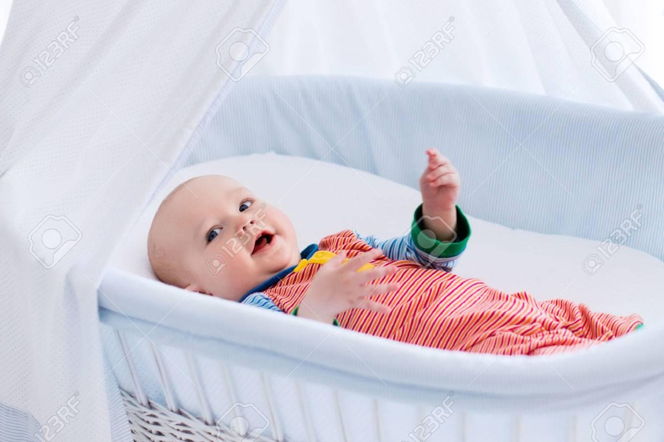 Lustige Baby In Weißen Krippe Mit Baldachin. Kinder Interieur Und Betten  Für Kinder. Lachender Kleiner Junge In Moses Korb Zu Spielen.