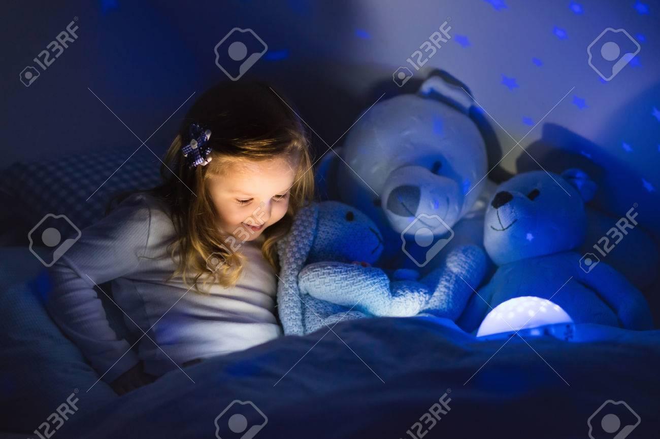 petite fille lisant un livre dans le lit. chambre sombre avec la