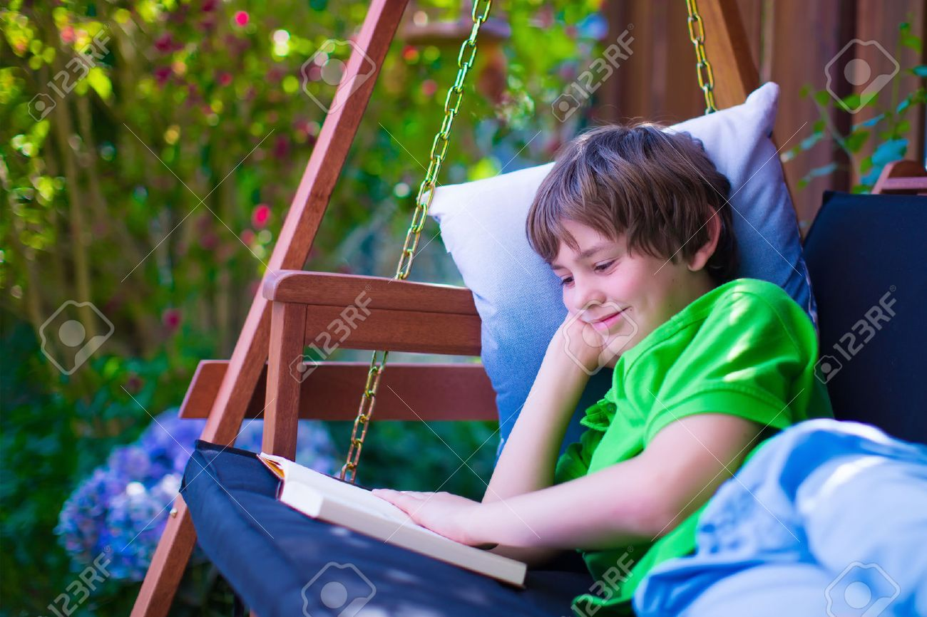 happy boy reading a book in the backyard child relaxing