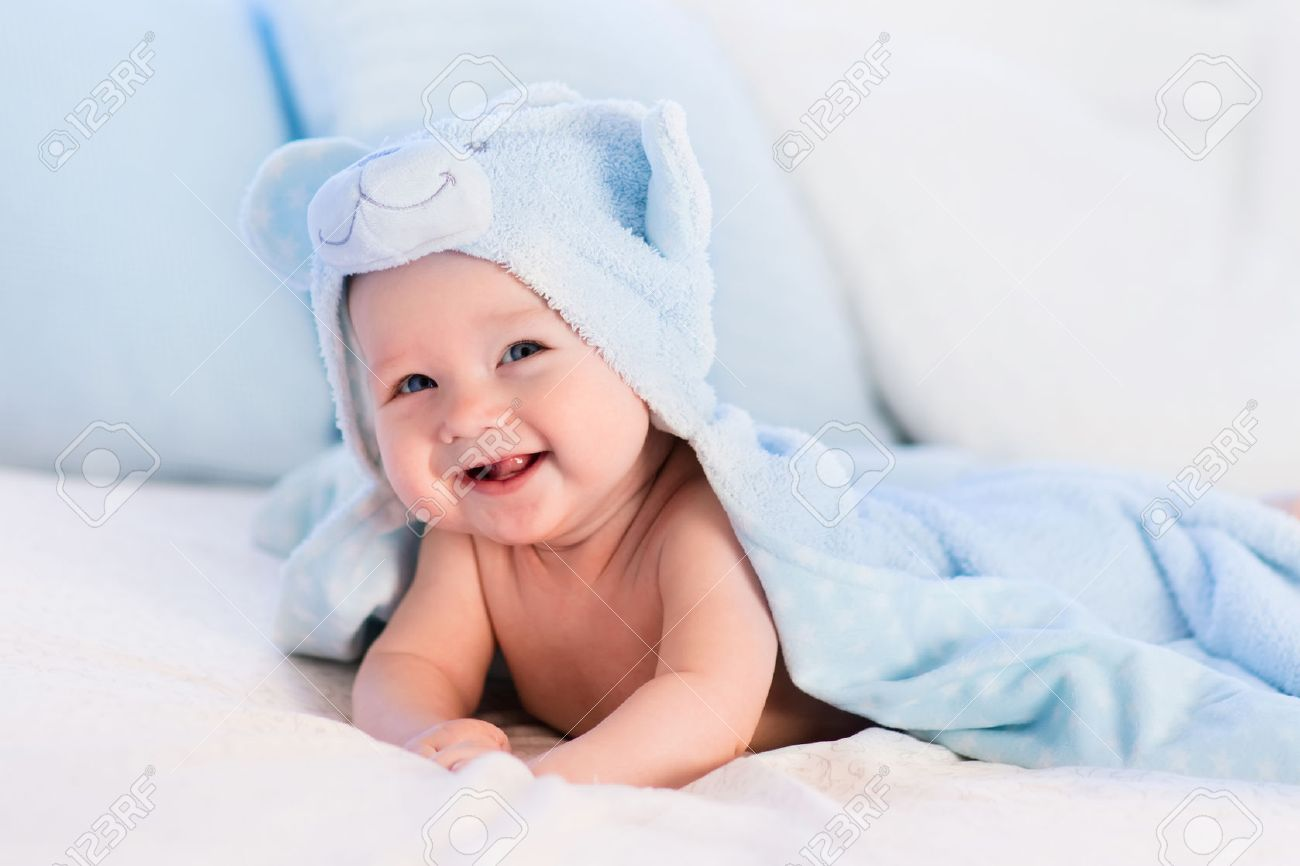 Baby boy wearing diaper and blue towel in white sunny bedroom. Newborn child relaxing in bed after bath or shower. Nursery for children. Textile and bedding for kids. New born kid with toy bear. Stock Photo - 54639940