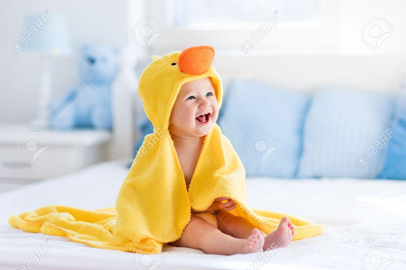 Happy laughing baby wearing yellow hooded duck towel sitting on parents bed after bath or shower. Clean dry child in bedroom. Bathing and washing of little kids. Children hygiene. Textile for infants. - 54640071