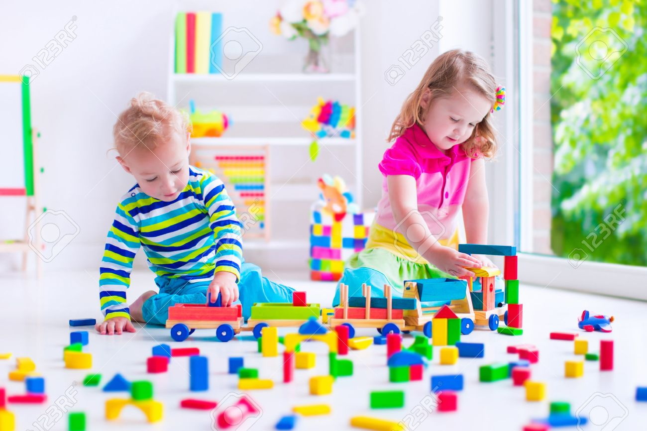 Kids play at day care. Two toddler children build tower of colorful wooden blocks. Child playing with toy train. Educational toys for preschool and kindergarten. - 54645401