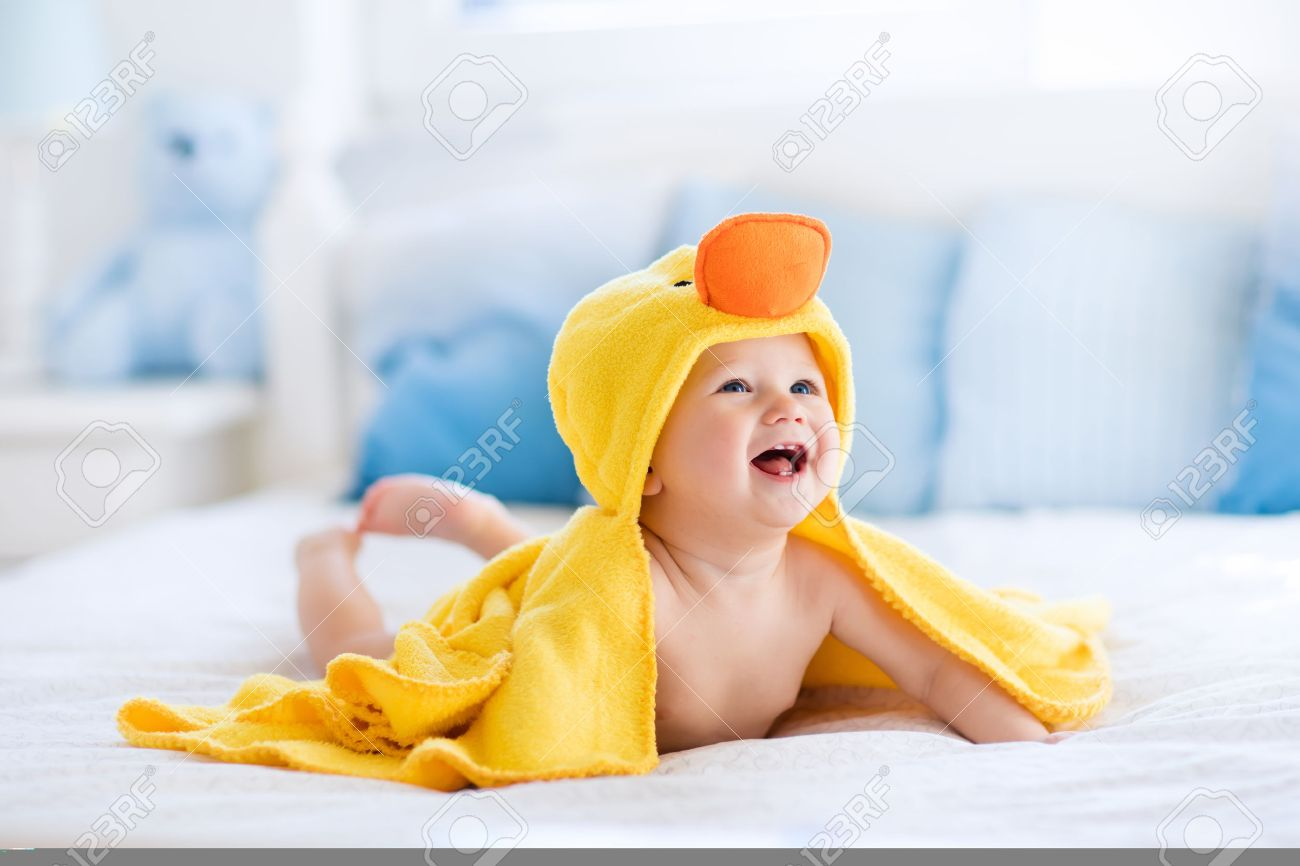 Happy laughing baby wearing yellow hooded duck towel sitting on parents bed after bath or shower. Clean dry child in bedroom. Bathing and washing of little kids. Children hygiene. Textile for infants. - 55198432
