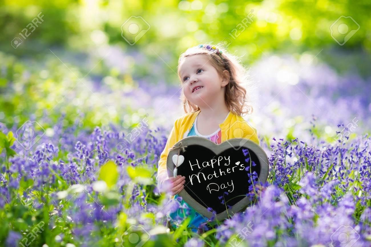 19fe5856b9a9e Enfant Jouant Dans Jacinthes Forêt. Petite Fille Tenant Un Bois En Forme De  C ur Panneau De Craie Debout Dans Un Parc Avec De Belles Fleurs Du Printemps  De ...