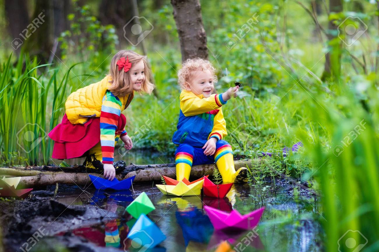 children play with colorful paper boats in a small river on a sunny spring day - Small Kids Images