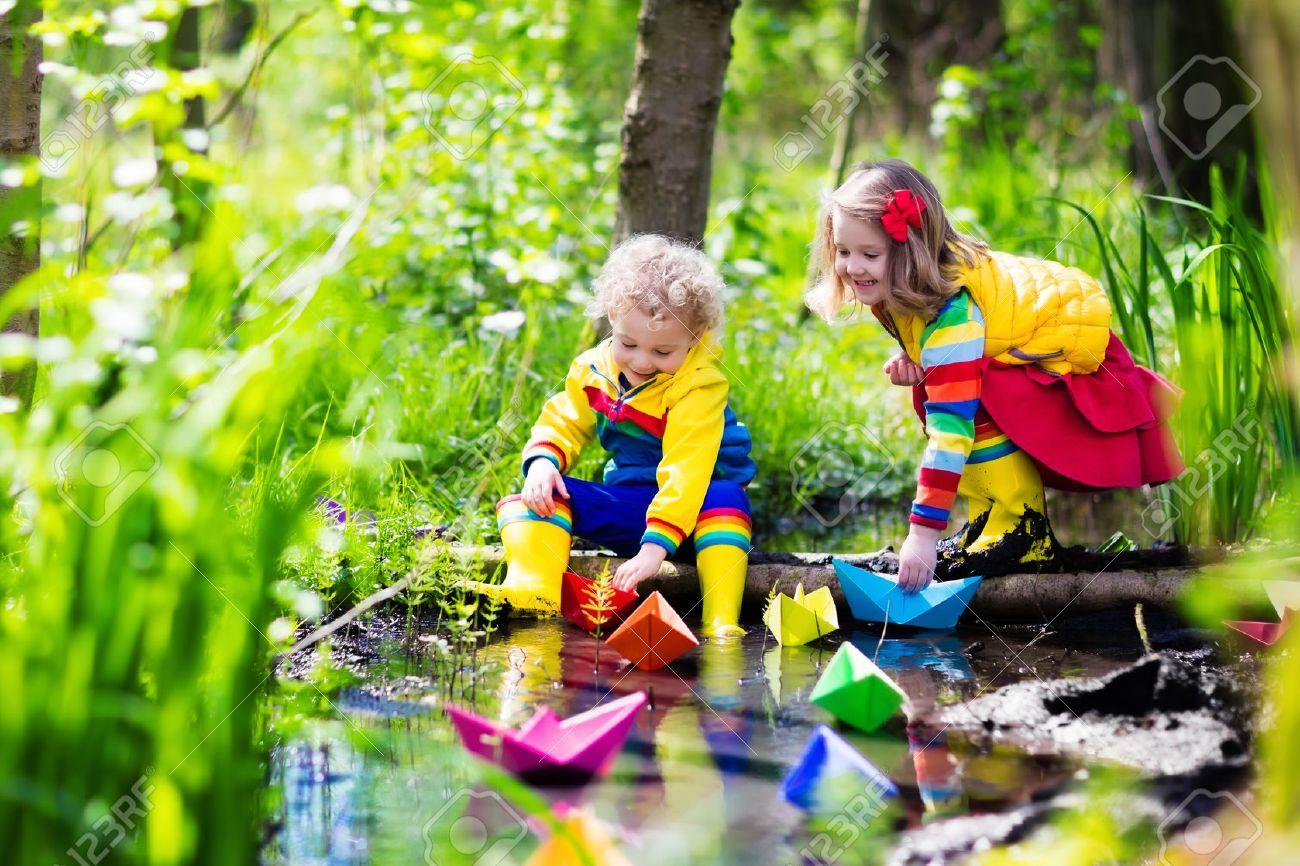 21605585cc676f Kinder Spielen Mit Bunten Papierboote In Einem Kleinen Fluss An Einem  Sonnigen Frühlingstag. Kinder Spielen Die Erkundung Der Natur.