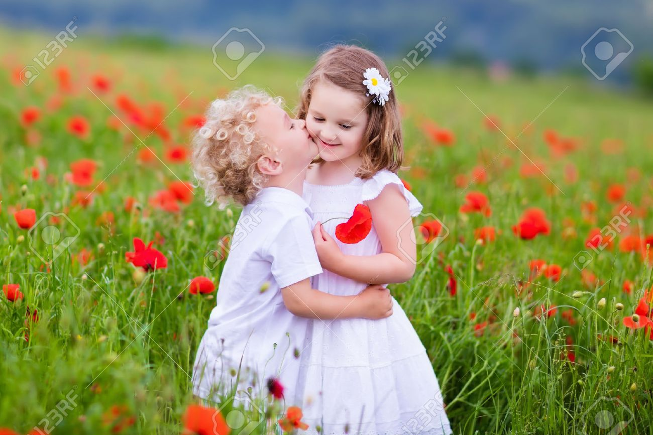 little curly blond boy and girl play in poppy flower field. child