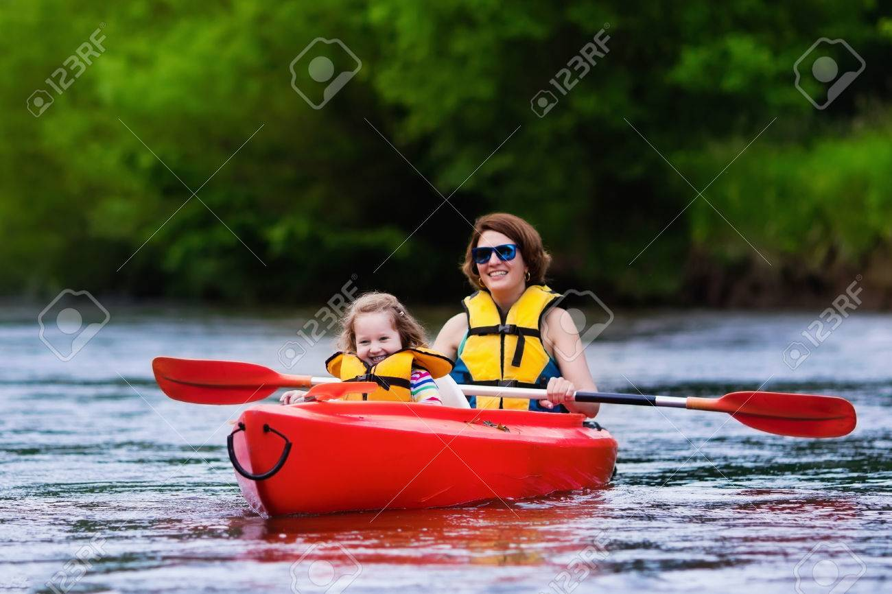 family on kayaks and canoe tour mother and child paddling in
