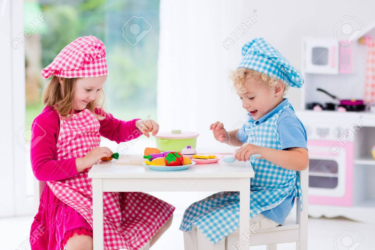 Little Girl And Boy In Chef Hat And Apron Cooking In Toy Kitchen.  Educational Toys