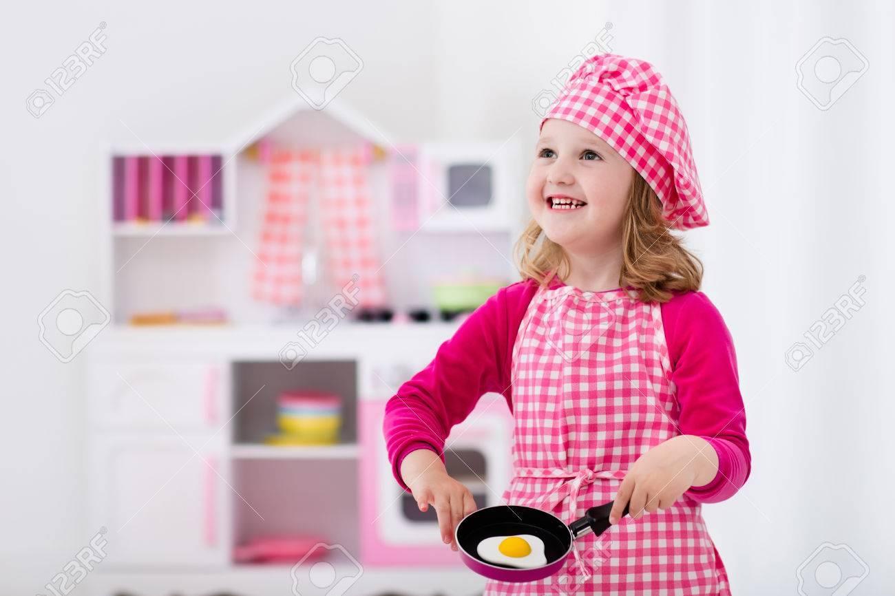 Kleines Mädchen Mit Kochmütze Und Schürze Kochen Eier In Spielzeug ...
