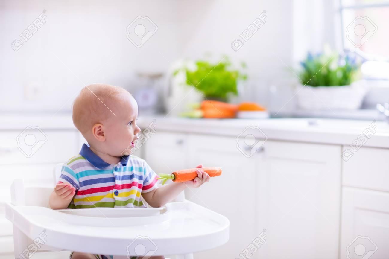 Happy Baby In Hochstuhl Sitzen Karotte In Einem Weißen Küche Essen ...