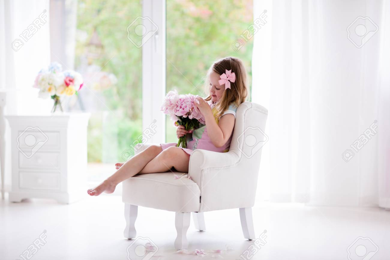 Little girl smelling peony flower bouquet sitting in a white..