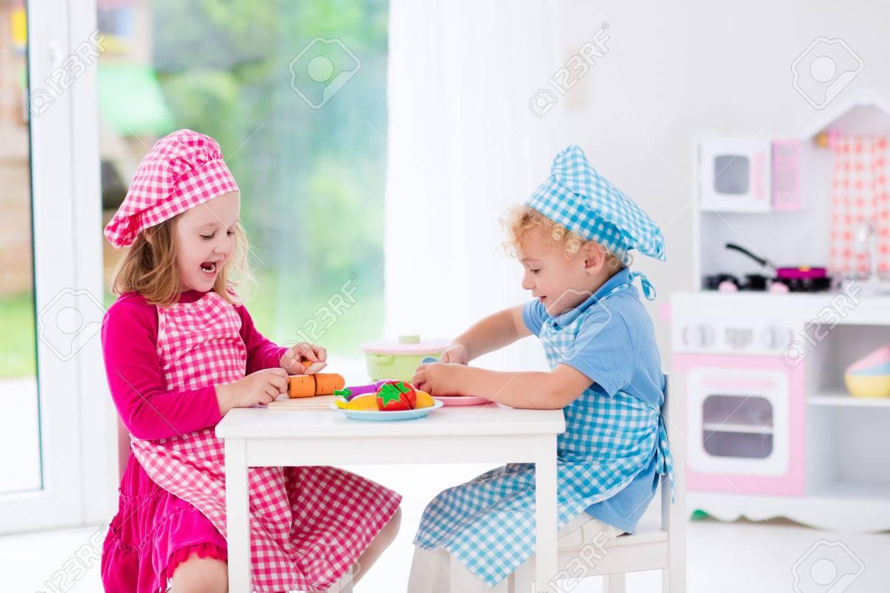 Kleine Mädchen Und Jungen In Kochmütze Und Schürze In Spielzeug ...