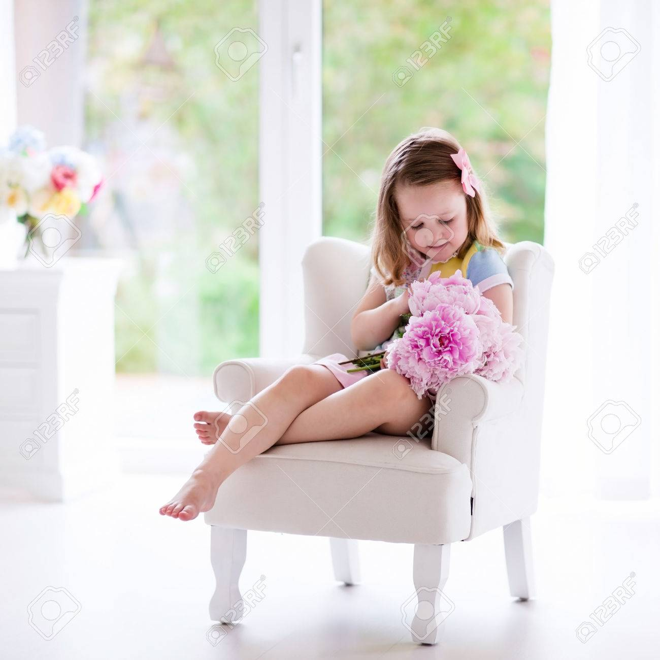 Little Girl Smelling Peony Flower Bouquet Sitting In A White Stock