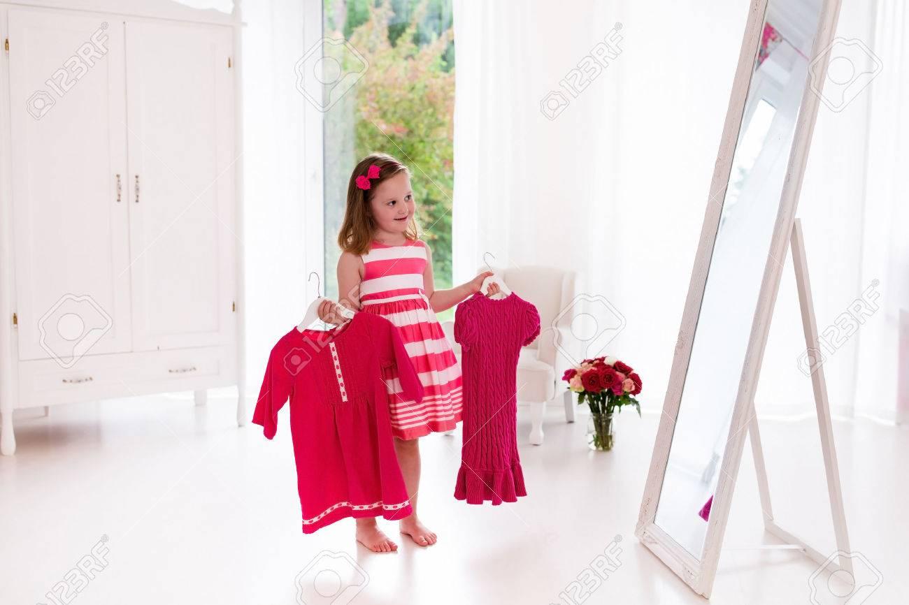 58965906 Petite Fille De Choisir Des Robes De Chambre Blanche Enfant  Regardant Le Miroir De Réflexion Tenant Ro