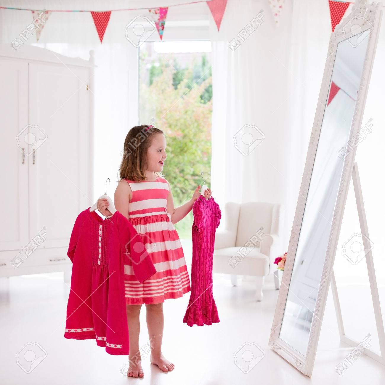 Petite Fille De Choisir Des Robes De Chambre Blanche Enfant Regardant Le Miroir De Reflexion Tenant Robe Rose Choix Tenue Pepiniere Filles Shopping Vetements Pour Les Enfants Inter Dressing Pour Les Enfants