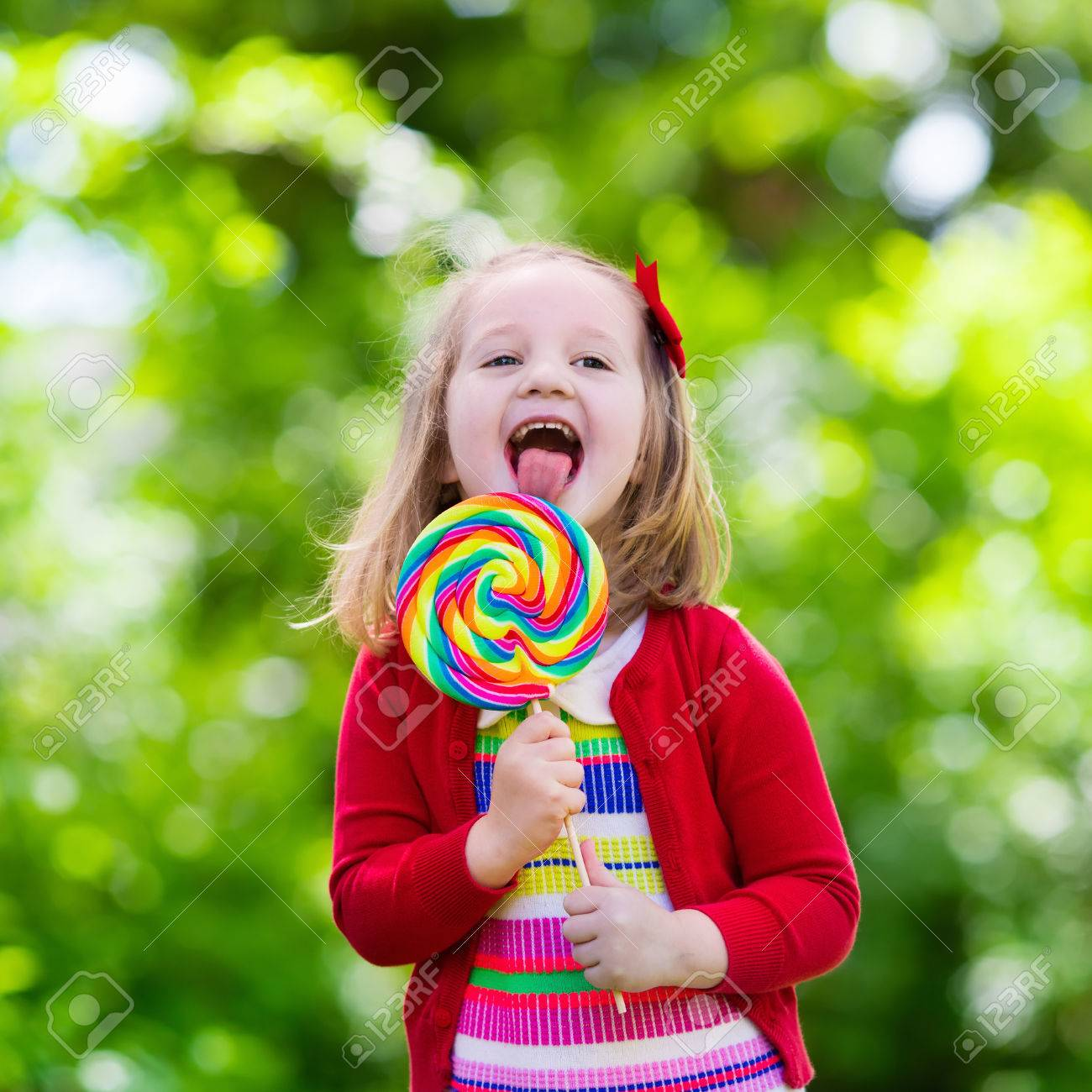 cute little girl with big colorful lollipop child eating sweet
