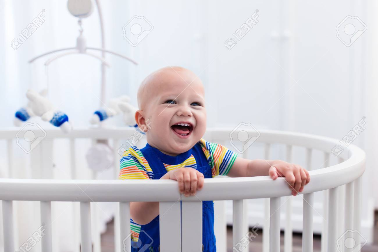 6ccab9bfe5bb Cute Laughing Baby Standing In A White Round Bed. White Nursery ...