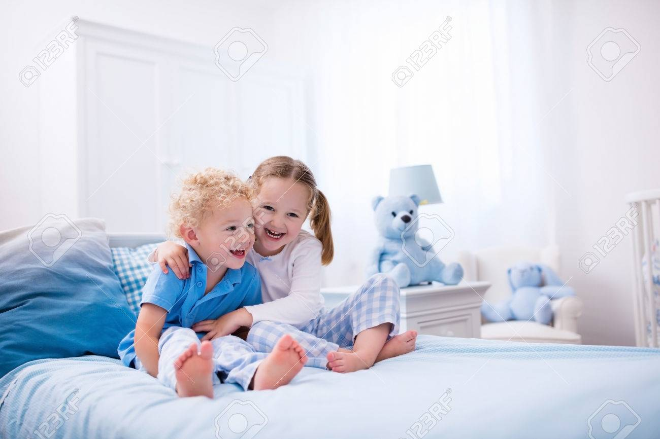 Happy Kids Playing In White Bedroom Little Boy And Girl Brother Stock Photo Picture And Royalty Free Image Image 59308566