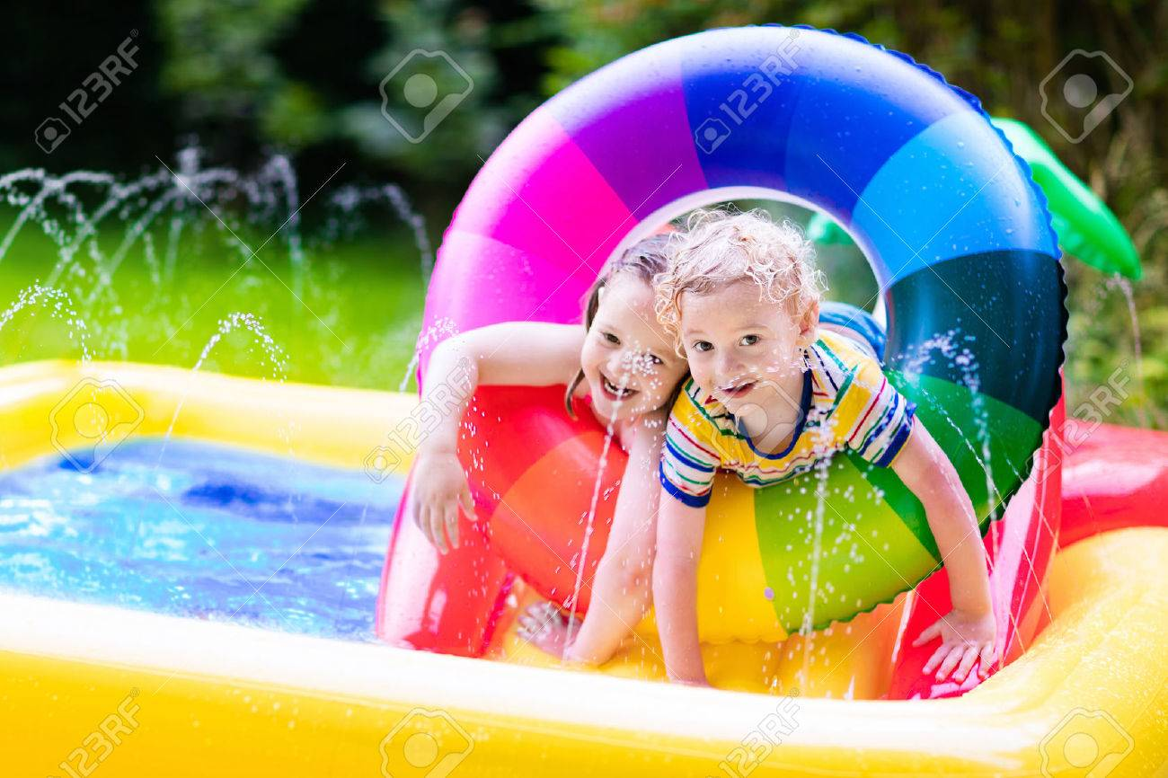 Children playing in inflatable baby pool. Kids swim and splash in colorful garden play center. Happy boy and girl playing with water toys on hot summer day. Family having fun outdoors in the backyard. - 59197374