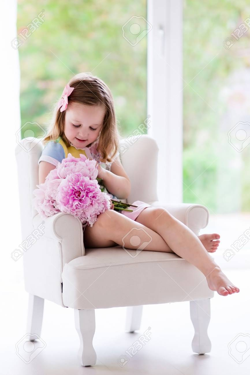Little Girl Smelling Peony Flower Bouquet Sitting In A White Chair