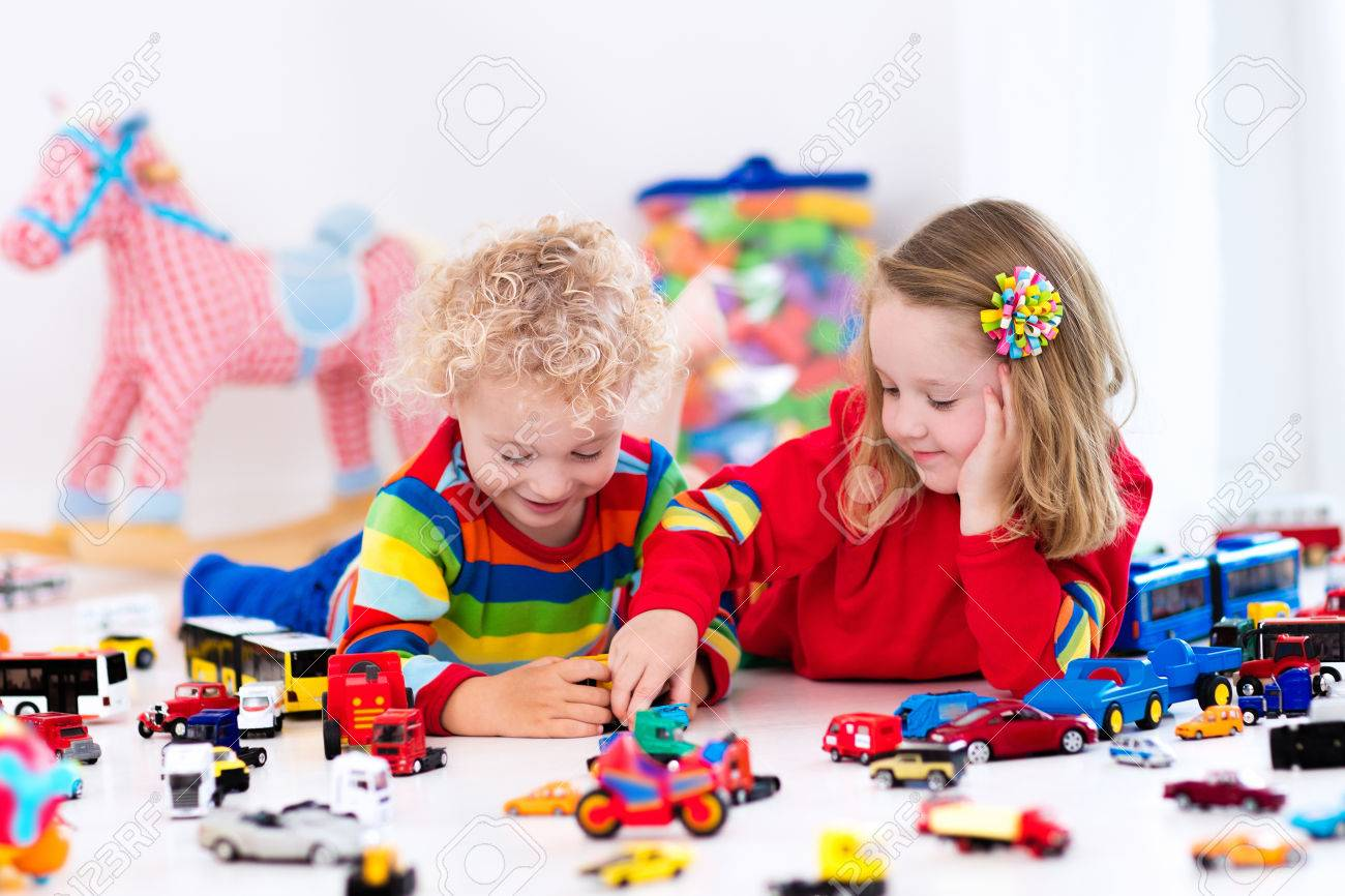 Little Toddler Boy And Girl Playing With Model Car Collection