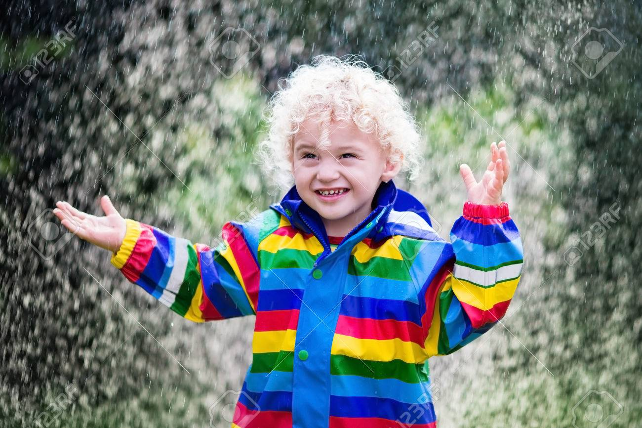 427be007f3d2cf Little blond curly boy in a waterproof jacket in rainbow color playing in  the rain.