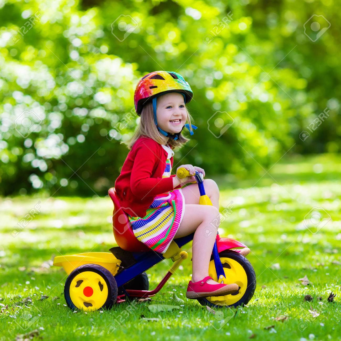 2d6efc6b676 Cute girl wearing safety helmet riding her tricycle in sunny summer park.  Kids ride bicycle. First bike for little child. Active toddler kid playing  and ...