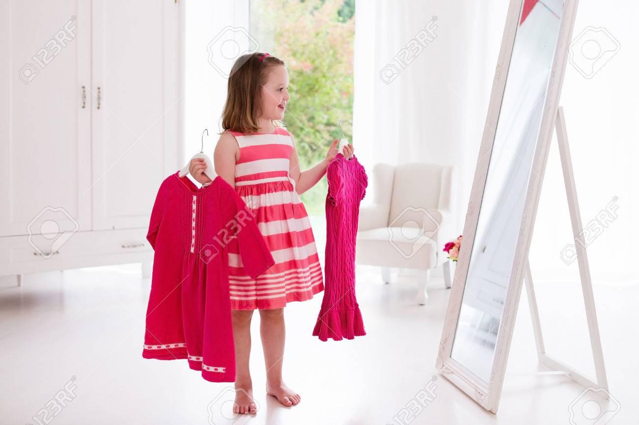 Niña Elección De Vestidos En El Dormitorio Blanco. Niño Que Mira La ...