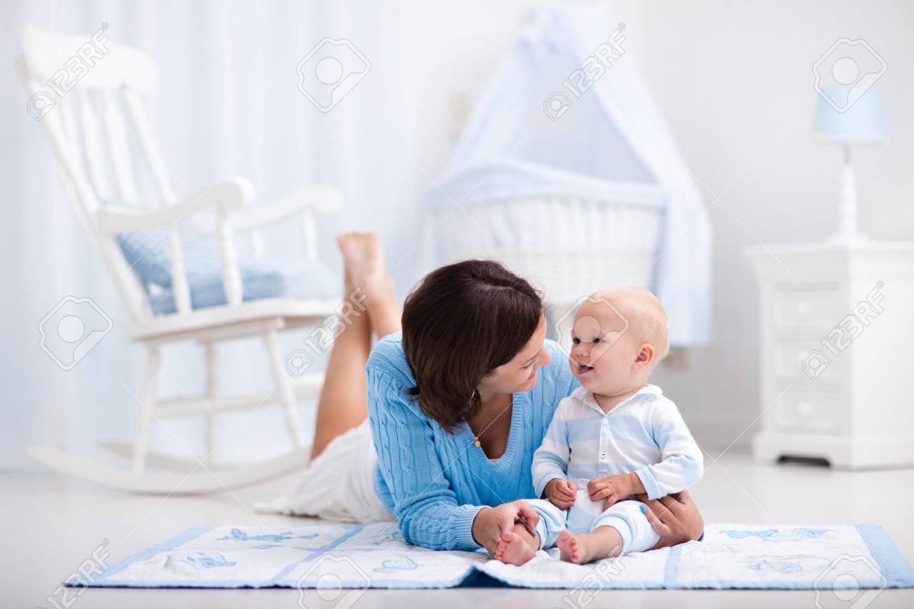 Feliz Madre Y Bebé Adorable Que Juega En Una Colchoneta Azul En Un ...