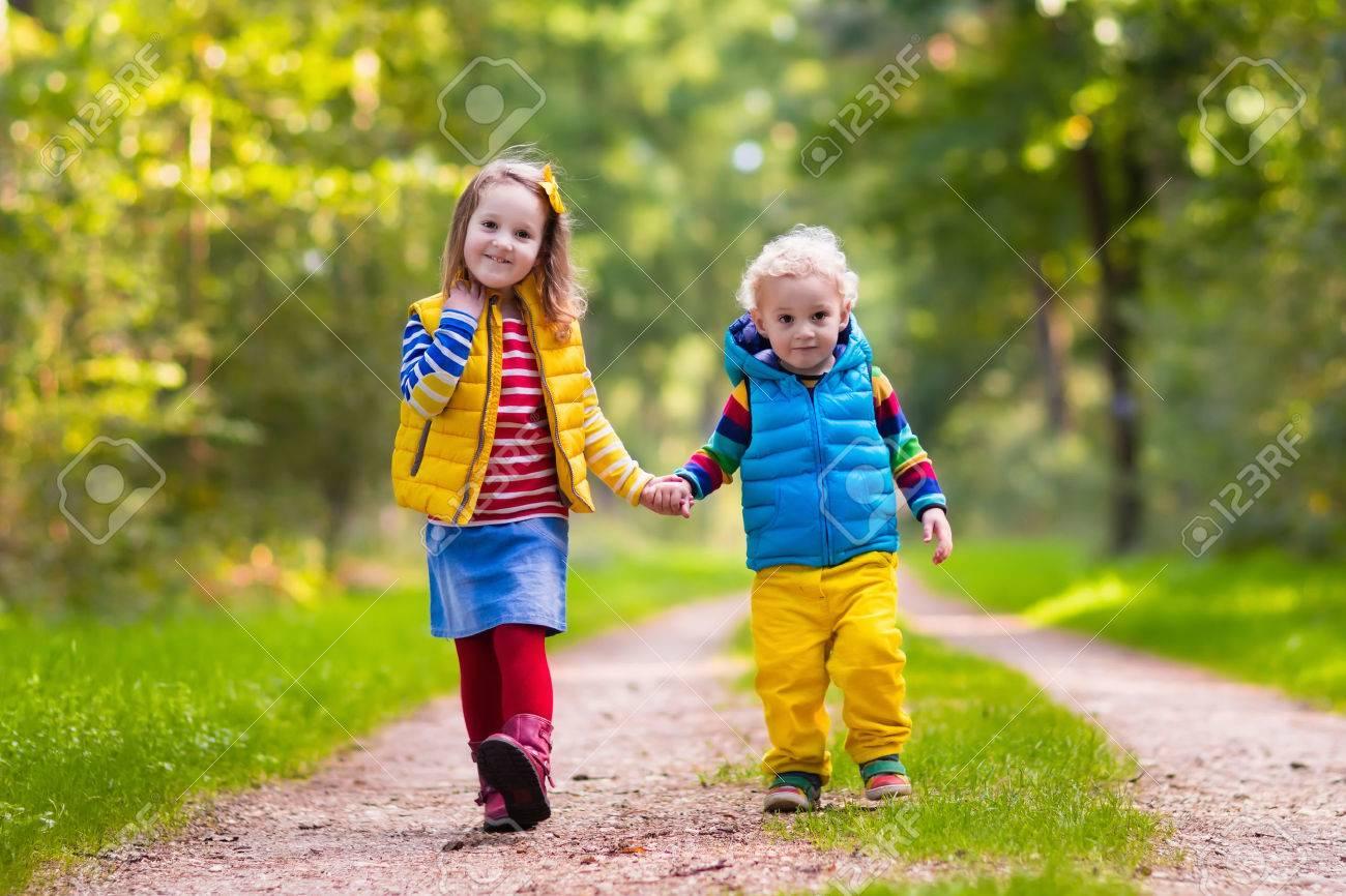 秋の公園で遊ぶ子供たち。子供の晴れた秋の日に外で遊ぶ。男の子と女の子