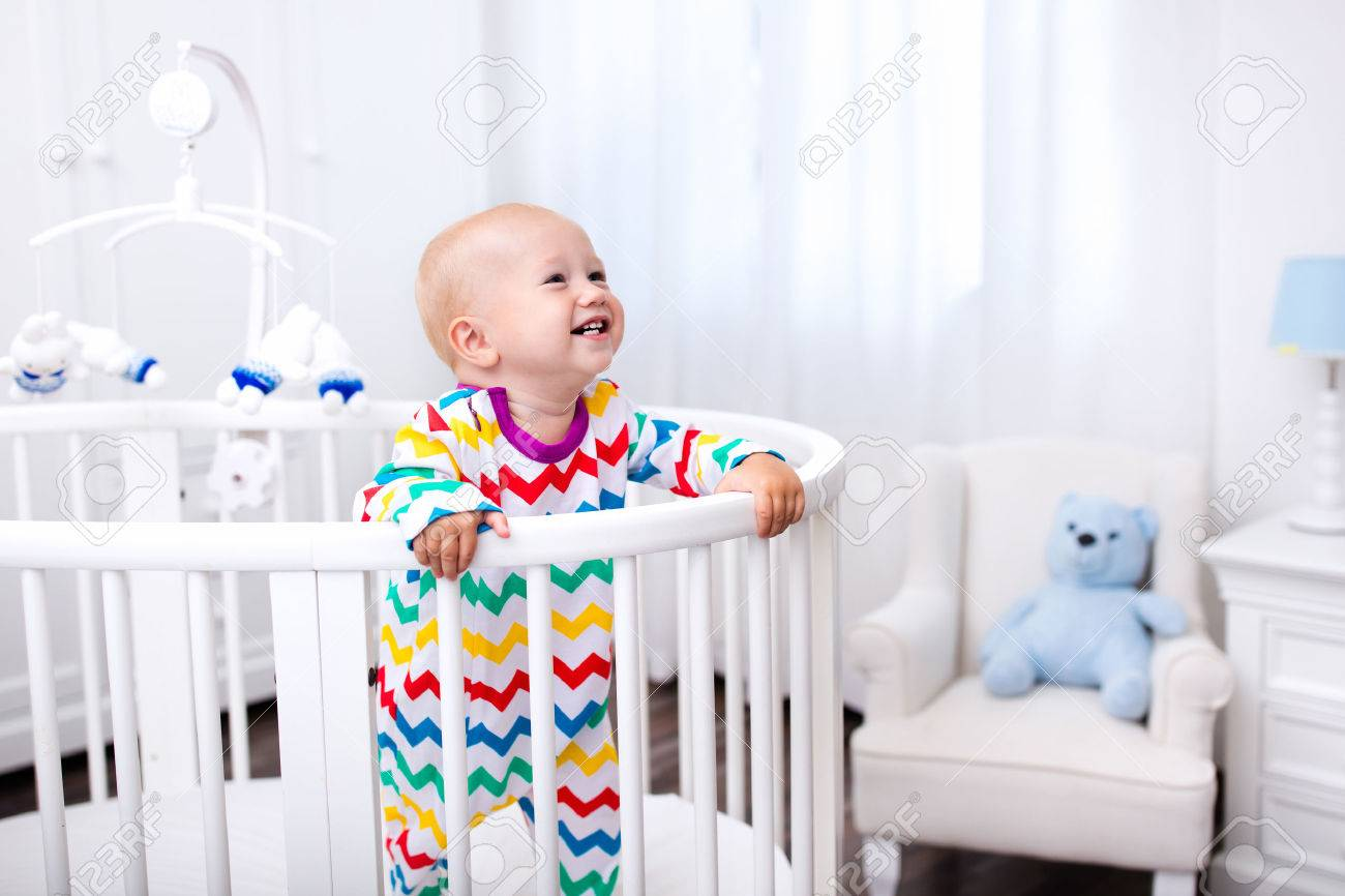 Cute laughing baby standing in bed after nap time. Nursery interior for young kids. Adorable little boy playing in his crib. White furniture for children bedroom. - 61386379