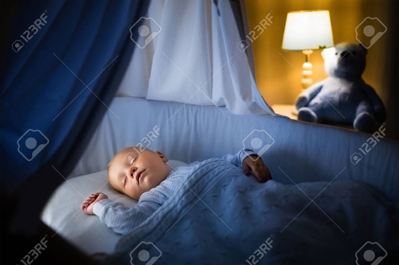 Entzückende baby nachts in blau bassinet mit baldachin schläft