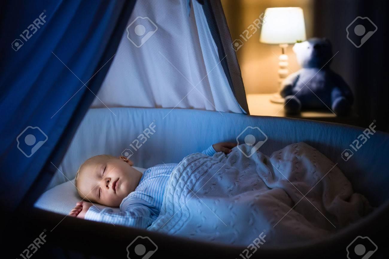 Schattige baby slapen in blauw wiegje met luifel s nachts. weinig