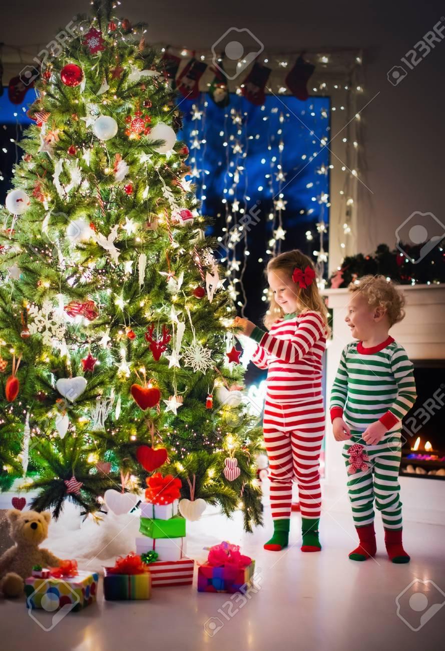 Happy Kleine Kinder In Passender Rot Grün Gestreiften Pyjama Schmücken  Weihnachtsbaum Im Schönen Wohnzimmer Mit